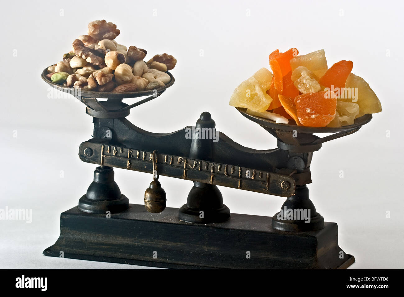Balance scale with a pile of cut fruit on one side and a pile of mixed nuts on the other - Stock Image