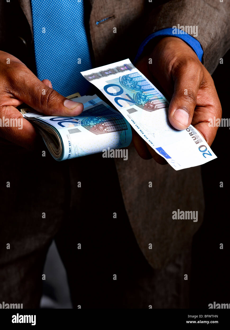 Business man with wad of euro bills - Stock Image