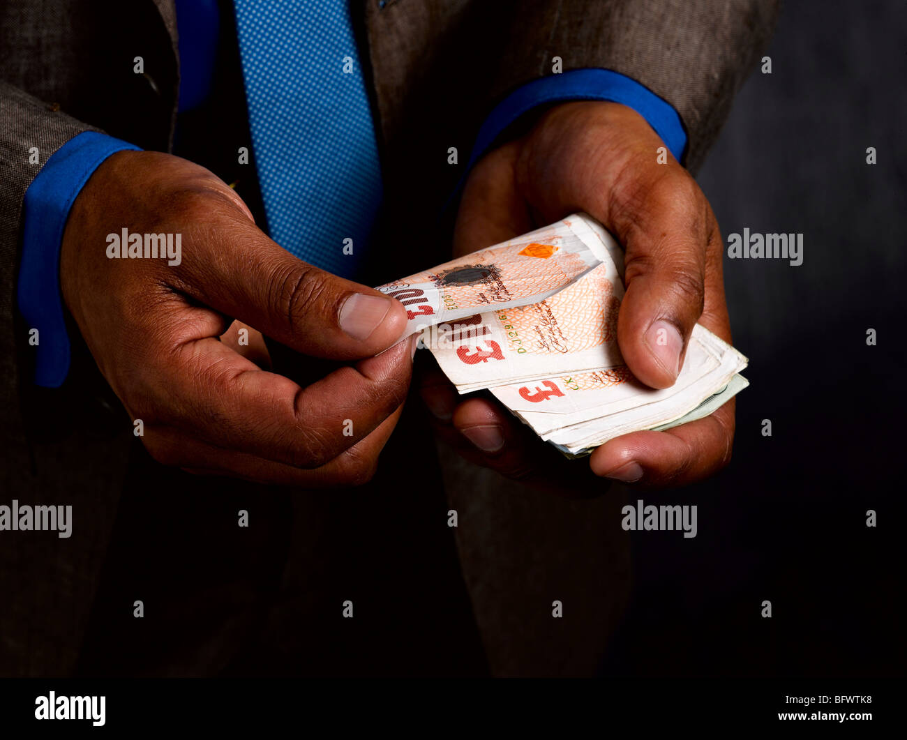 Business man with wad of sterling notes - Stock Image