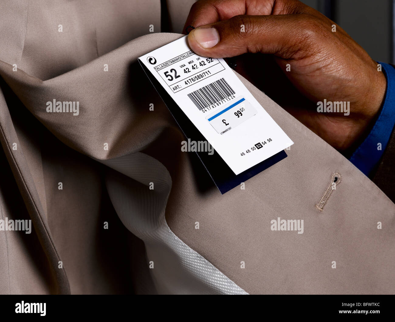 Business man looking at price tag - Stock Image