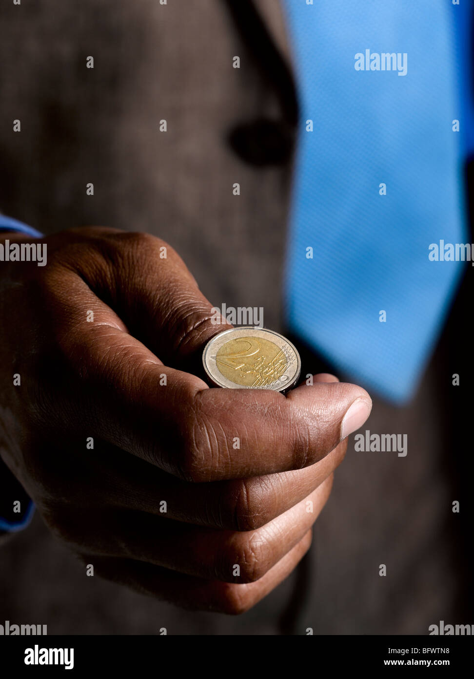 Business man ready to flip euro coin - Stock Image