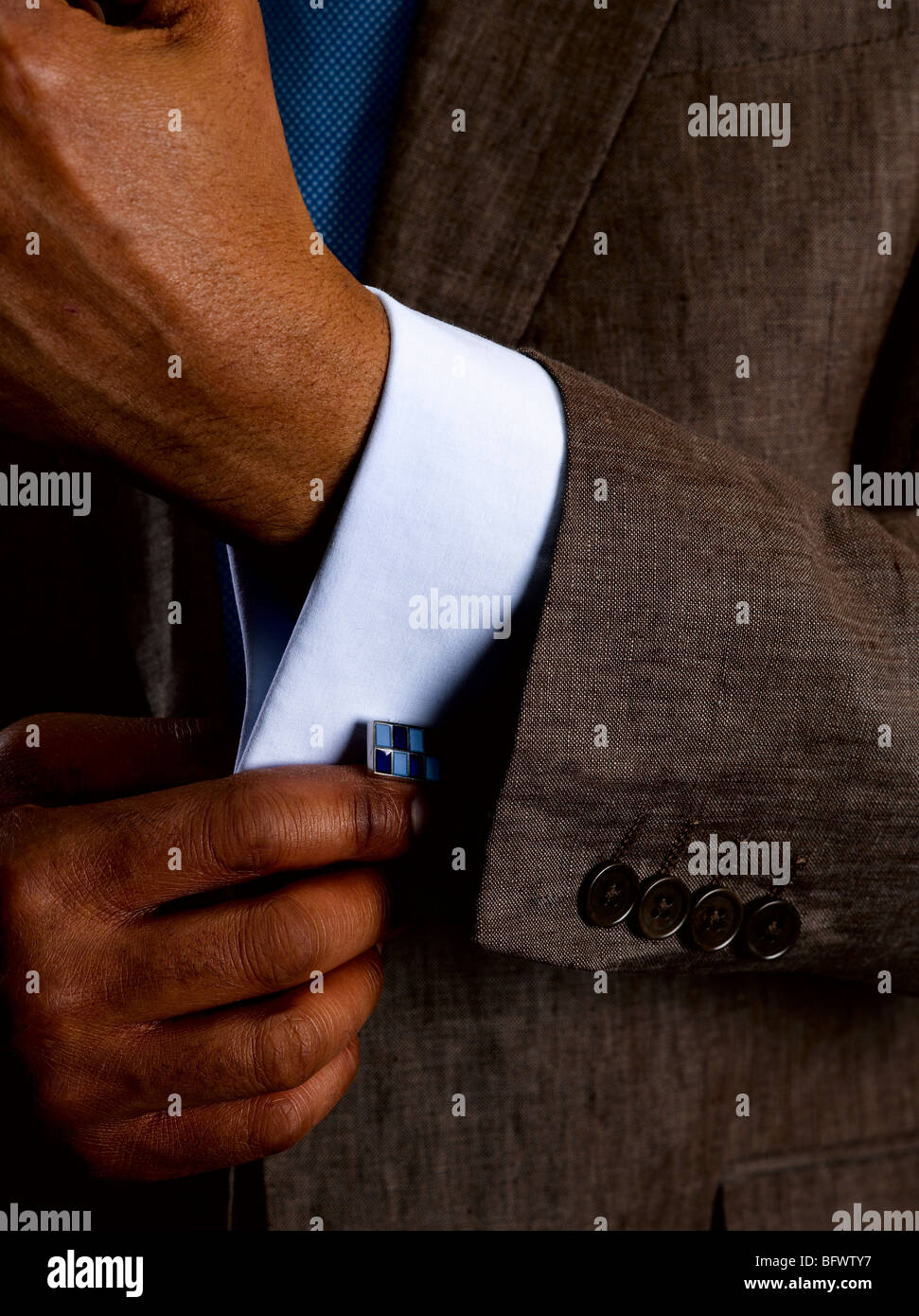 Business man adjusting cuff links - Stock Image
