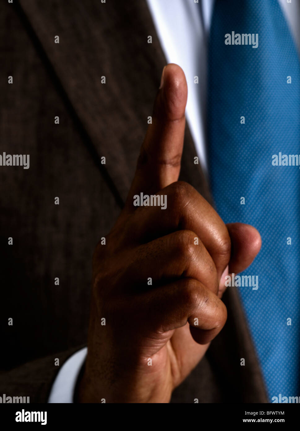 Business man holding one finger up - Stock Image