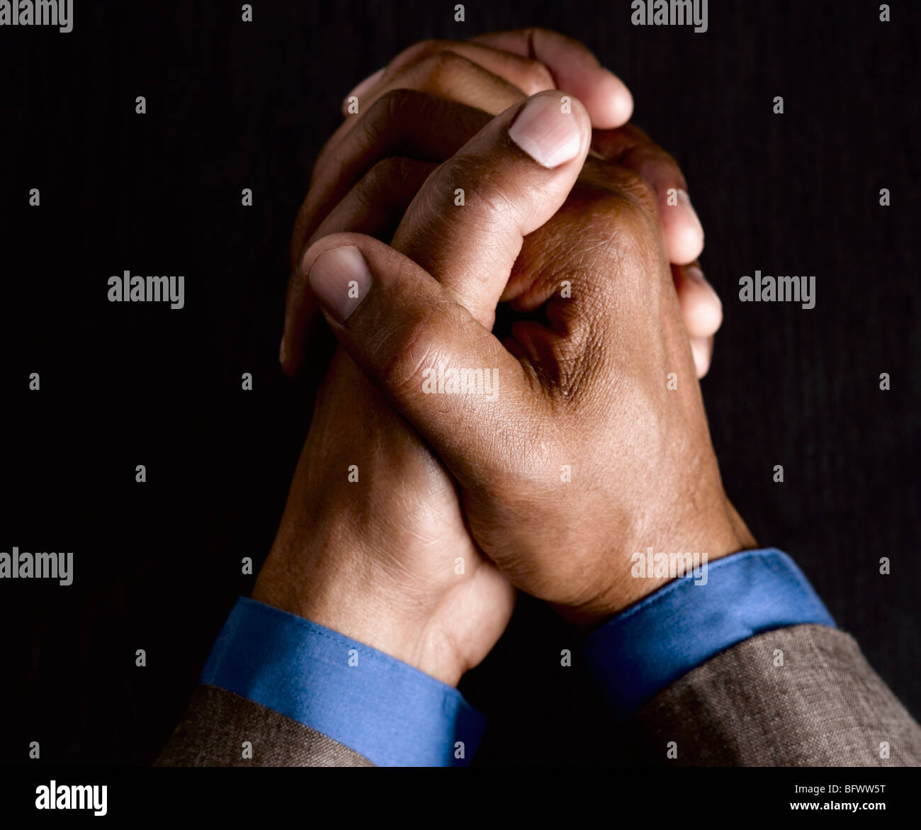 Business man with hands clasped together - Stock Image