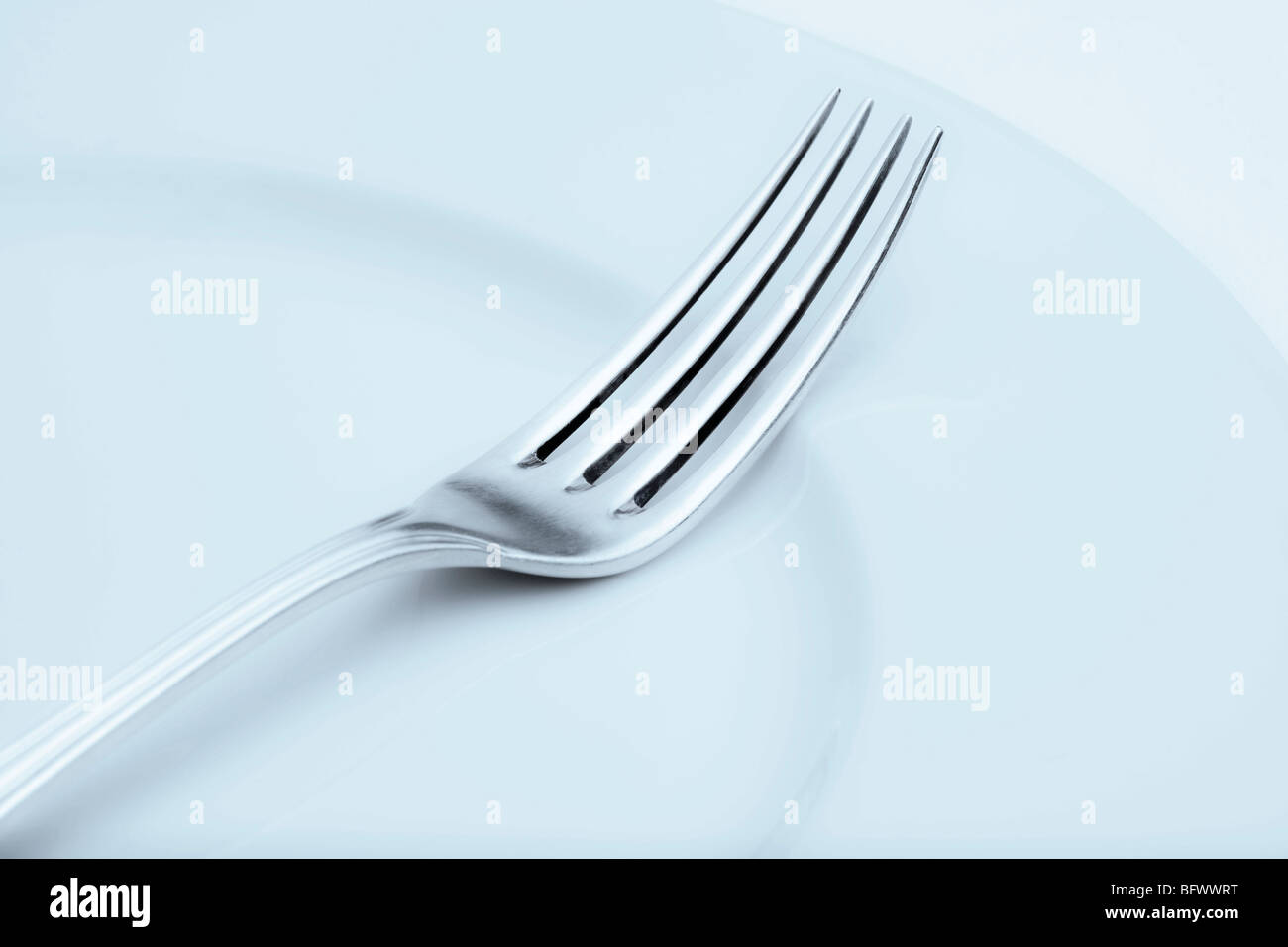elegant table setting with silverware and plate-closeup of a fork - Stock Image