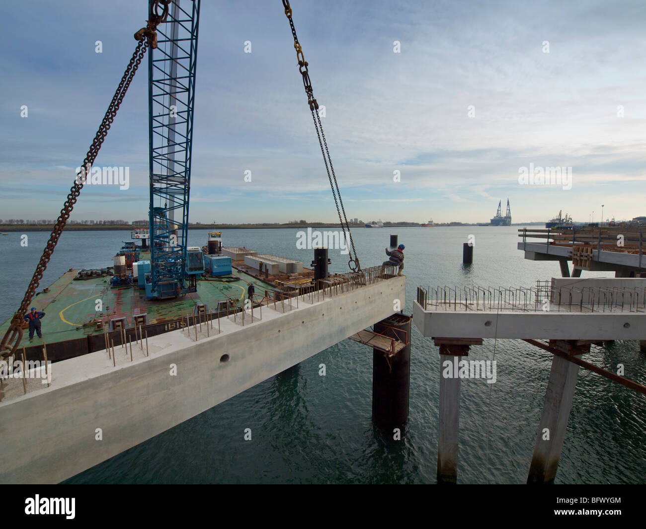 Large floating crane lifting a concrete block into place while building a docking station pier for a large petroleum - Stock Image