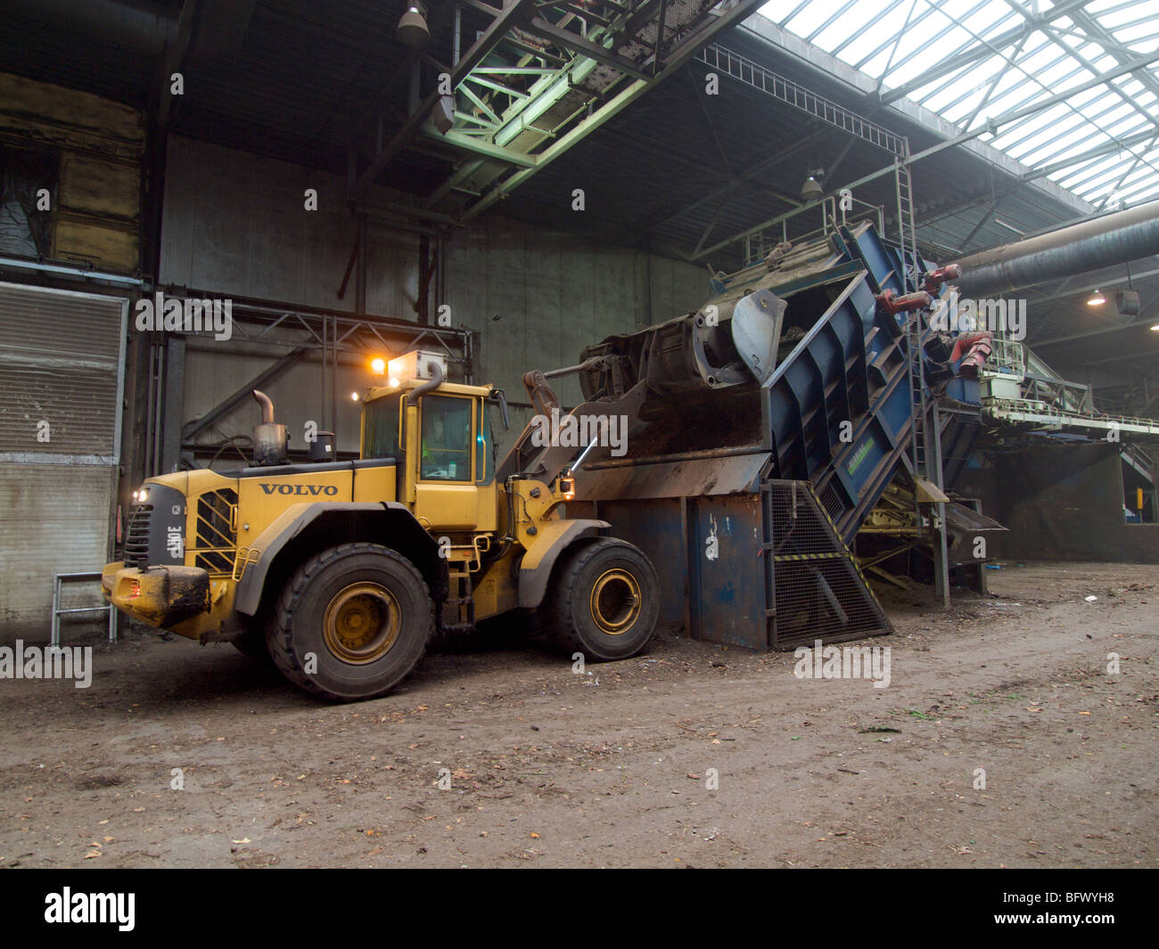 Large Volvo shovel dumping load of organic garbage into shredder at composting plant - Stock Image