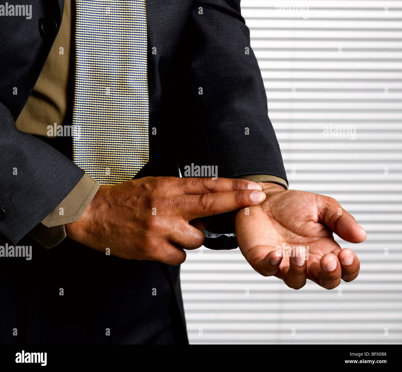 Business man with finger on pulse - Stock Image