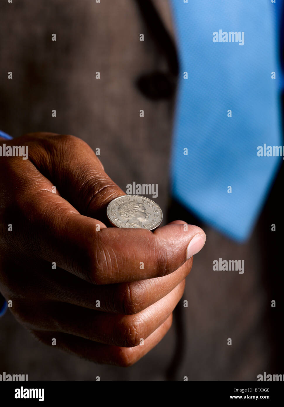 Business man ready to flip sterling coin - Stock Image