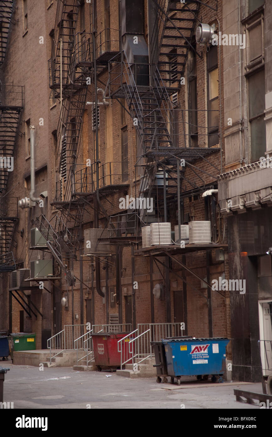 trash dumpster garbage dustbins and fire escape stairwells staircases in a back alley in inner city america usa - Stock Image