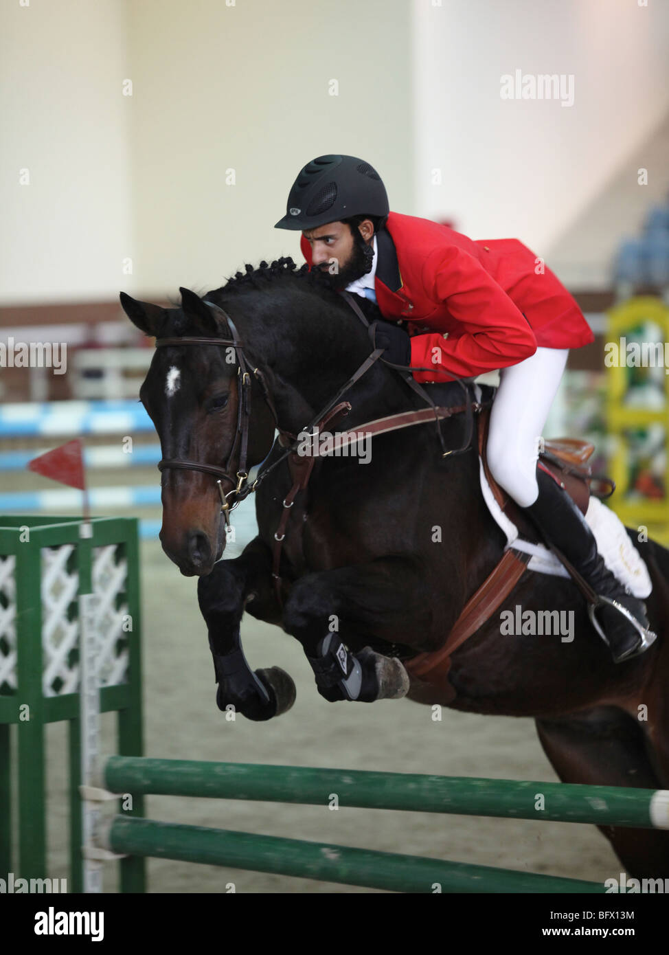 A regional showjumping competition at the Qatar Equestrian Federation's indoor arena in Doha - Stock Image