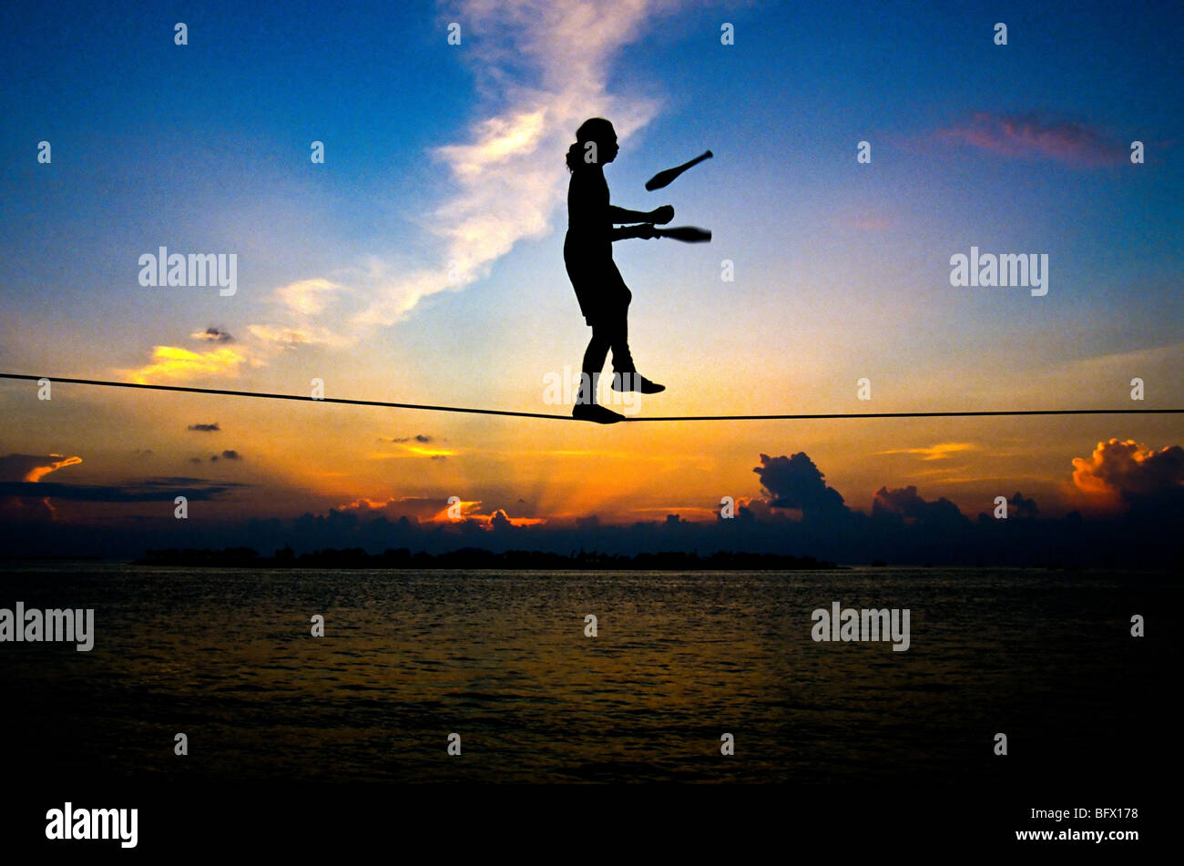 A tightrope walker performs during the sunset celebration at Mallory Square in Key West Florida. - Stock Image