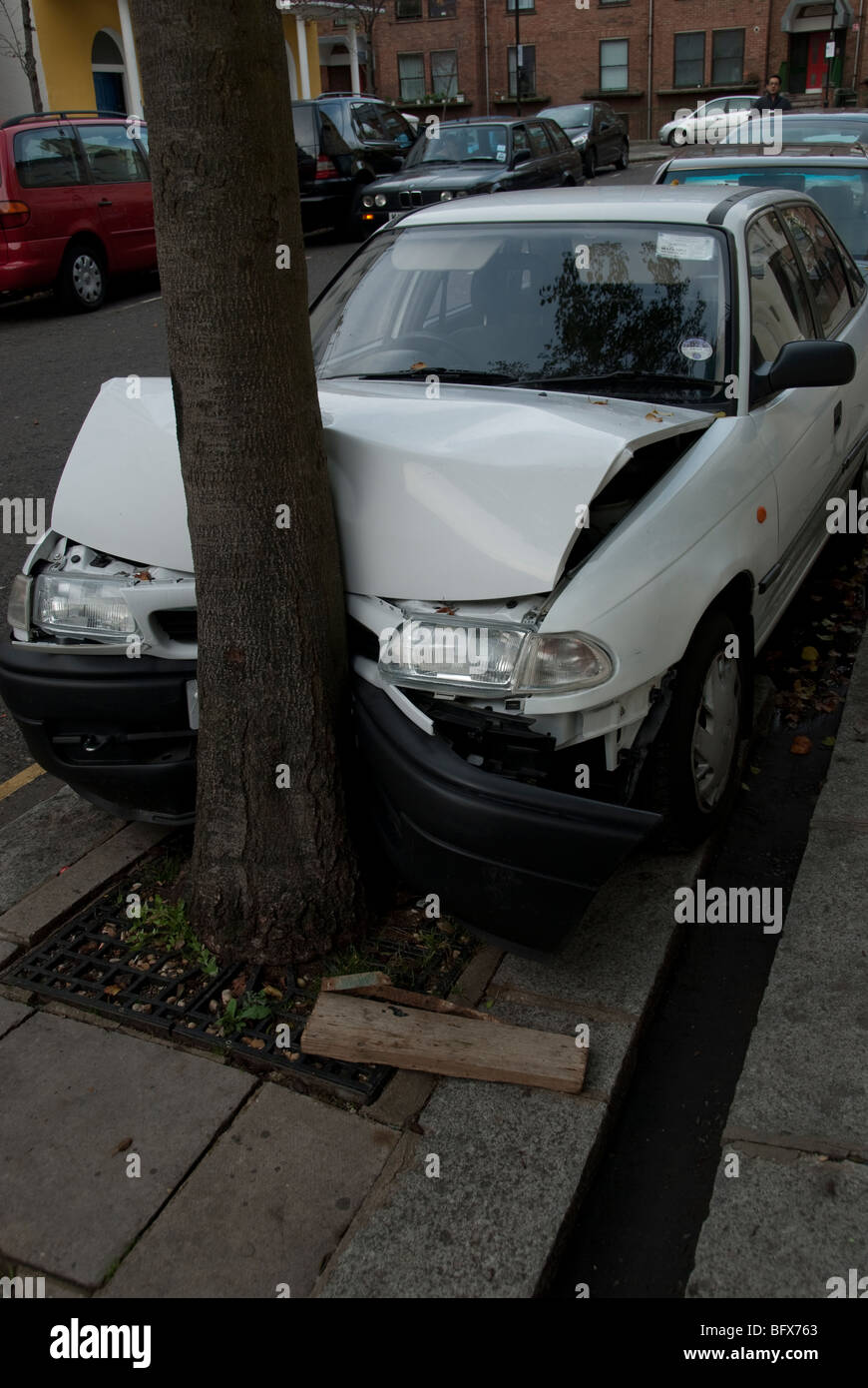 parked white car pushed around tree by another car - Stock Image