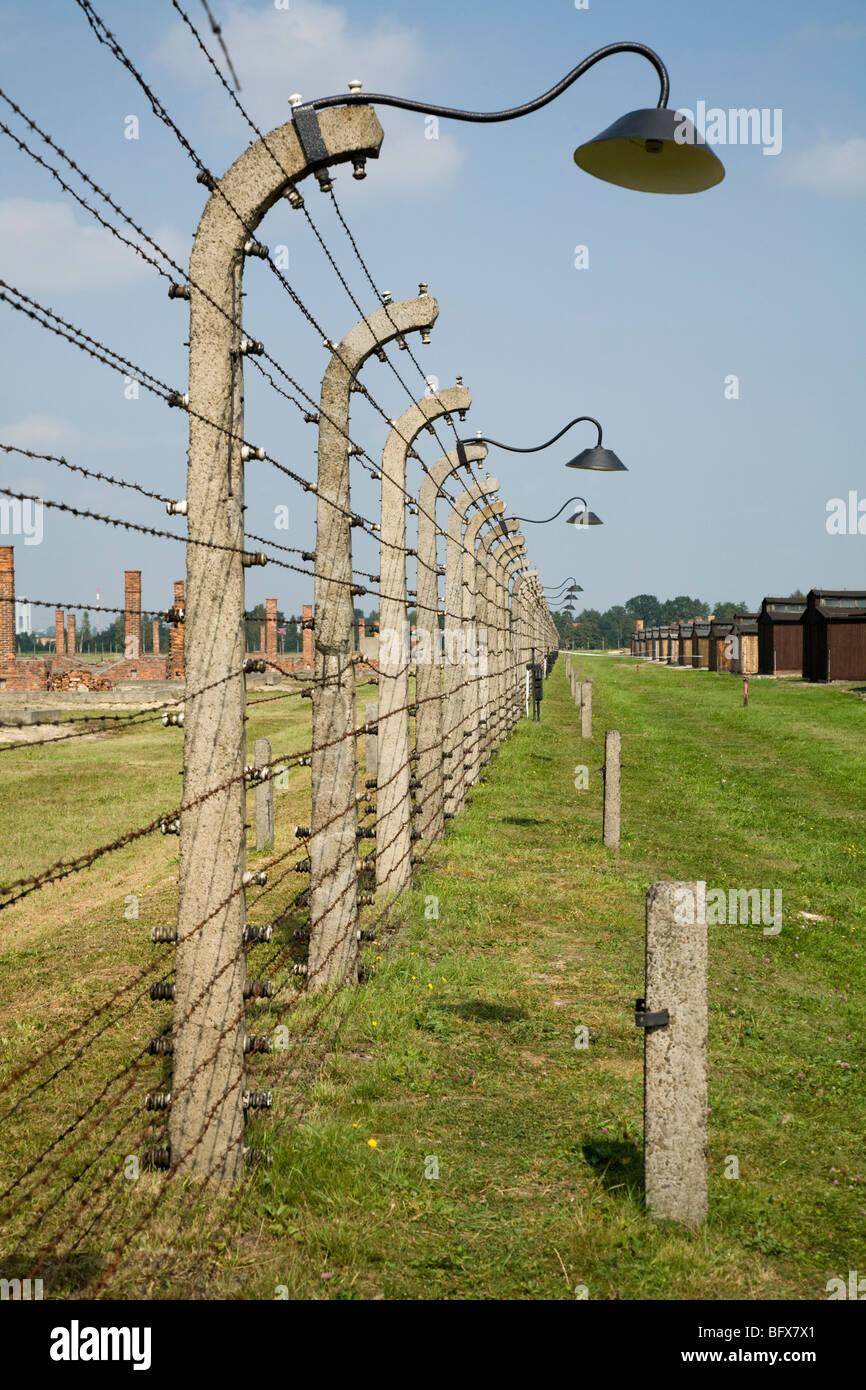 Perimeter fence / Birkenau (Auschwitz II Birkenau) Nazi death camp in Oswiecim, Poland, & brick chimneys from - Stock Image