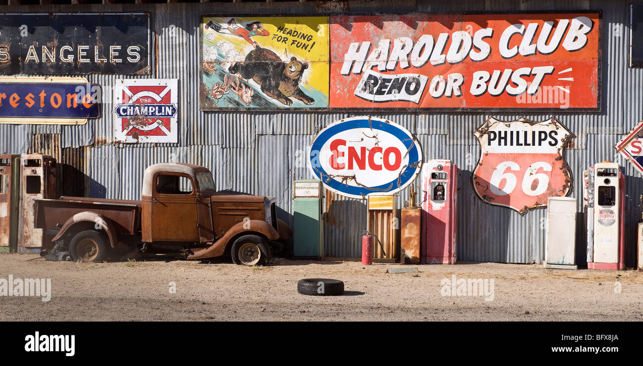 Junkyard with Old Oil Industry Signs and rusted car - Stock Image