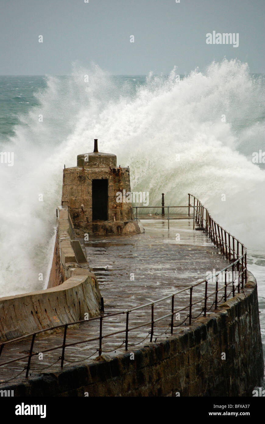 waves crashing against the old pier at portreath in cornwall, uk - Stock Image