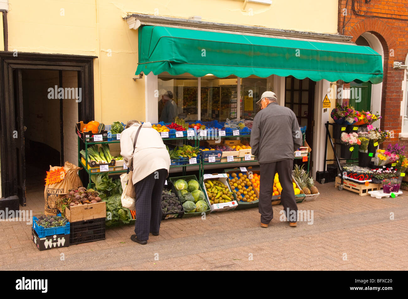 A greengrocers shop store with people choosing their fruit & veg in the high street in Halesworth,Suffolk,Uk - Stock Image