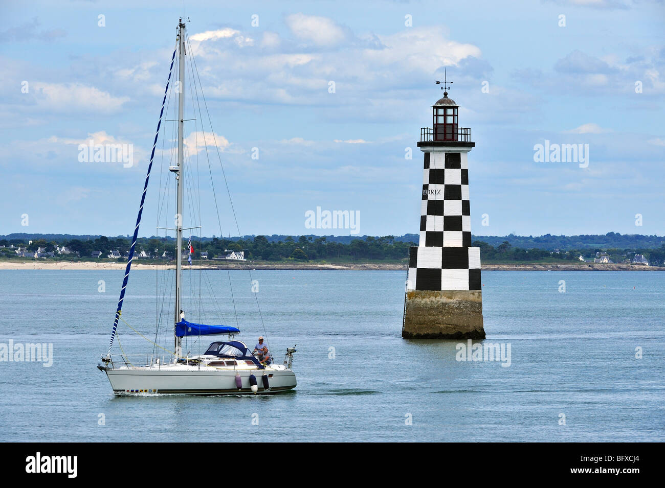 Sailing boat and the lighthouse Perdrix at Loctudy, Finistère, Brittany, France - Stock Image