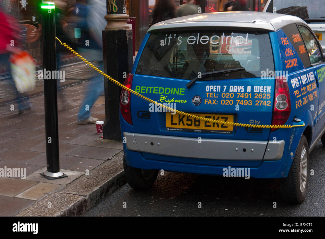 An electric car on charge at a charging and parking bay in Berkley Square London - Stock Image