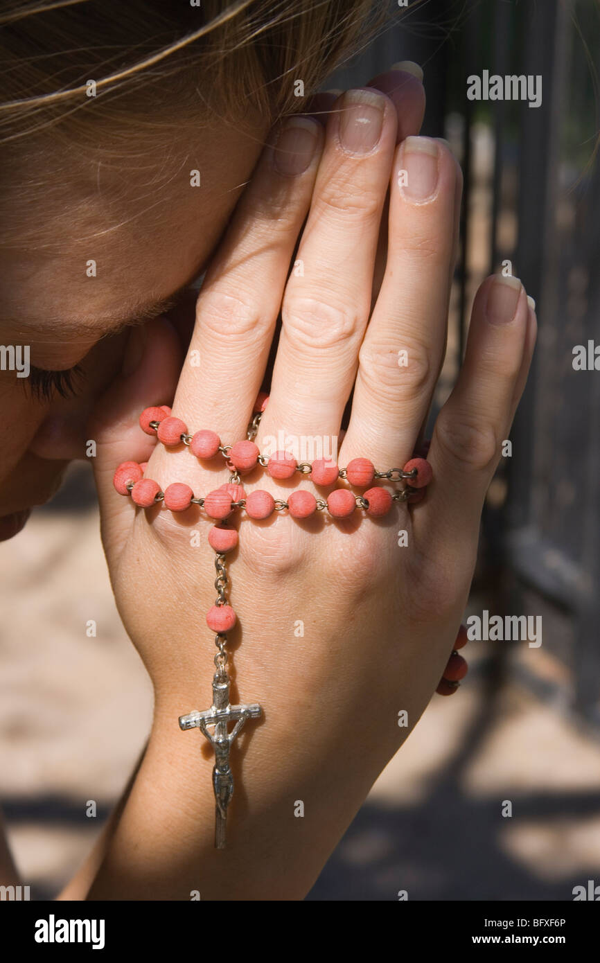 Young woman praying with rosary beads in her hands. - Stock Image