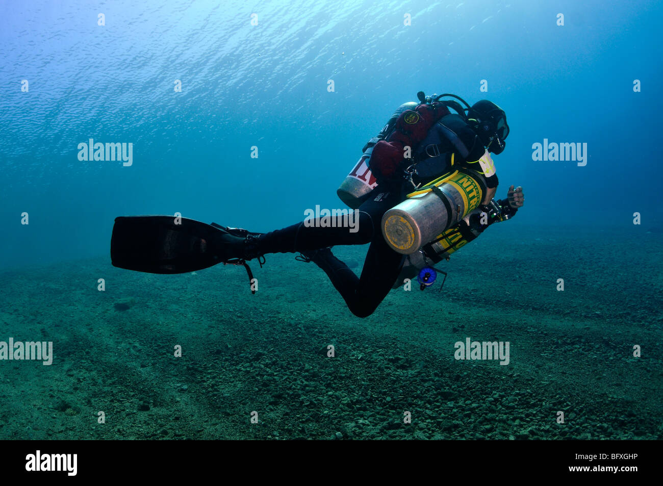 Technical scuba diver with multiple cylinders in shallow water, 'Red Sea' - Stock Image