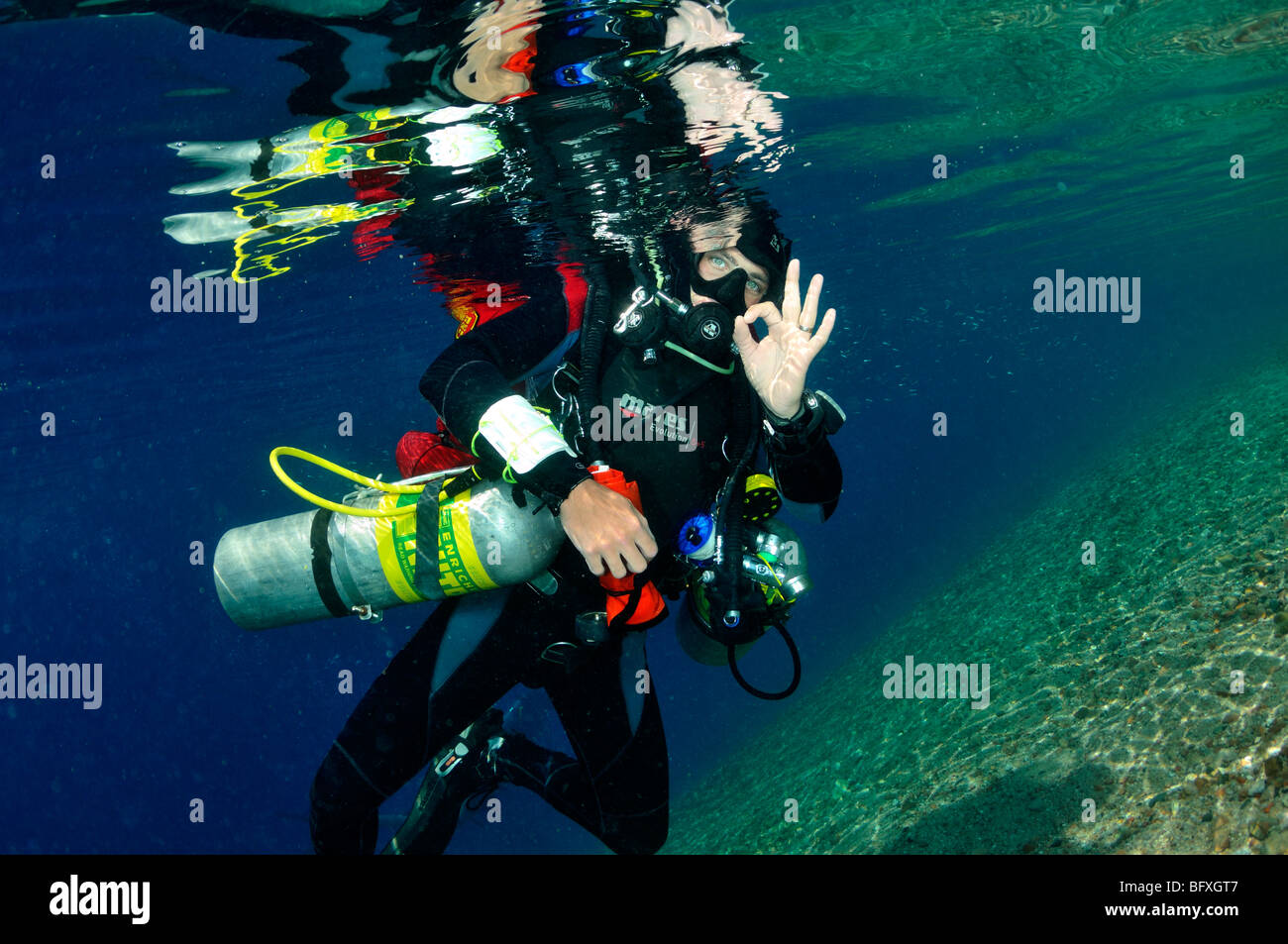 Technical scuba diver with multiple cylinders at surface giving 'OK' sign Ras Abu Gallum, 'Red Sea' - Stock Image