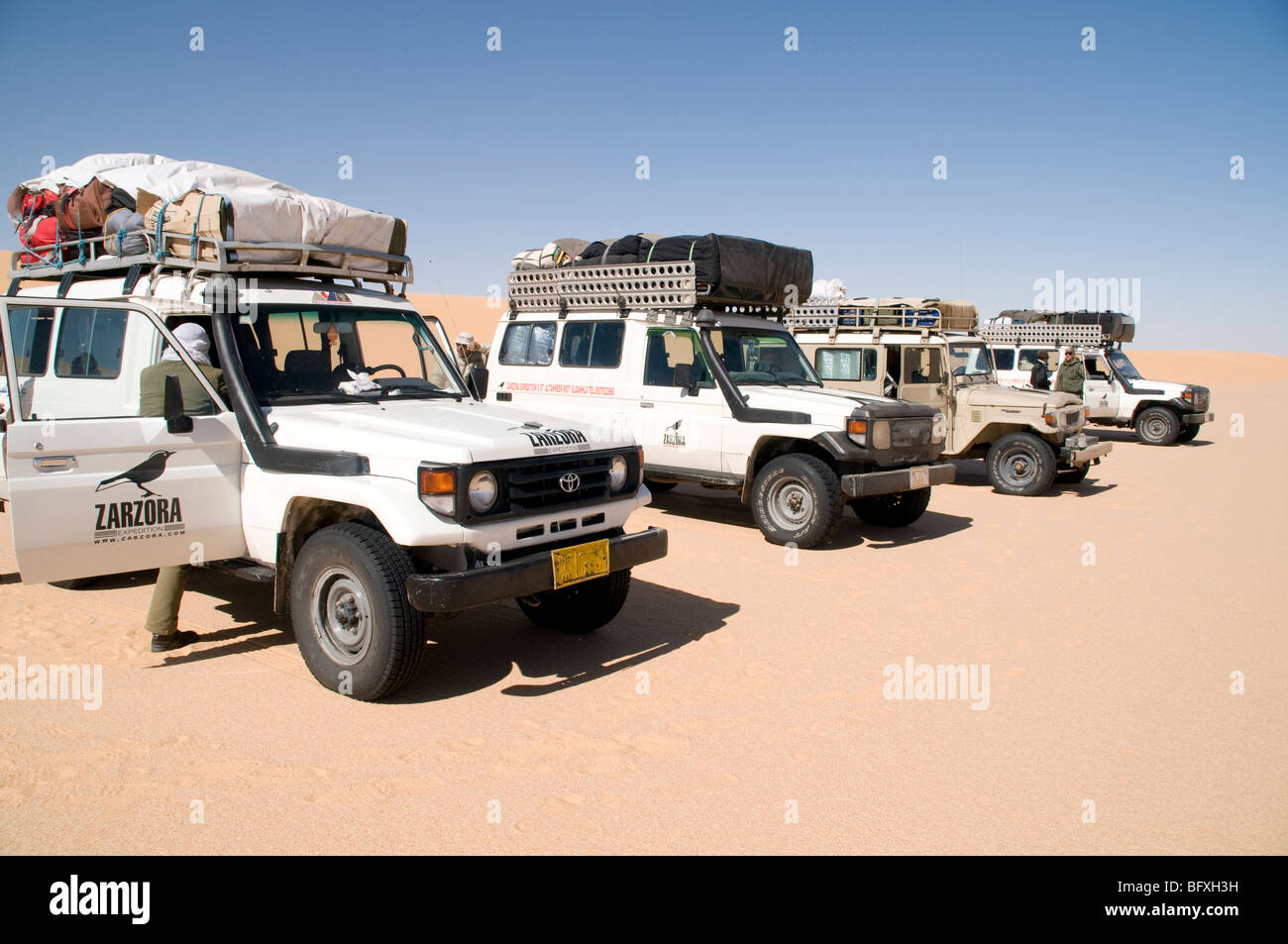 A convoy of Sahara desert safari 4x4 jeeps on the edge of the Great Sand Sea deep in the Western Desert region of - Stock Image