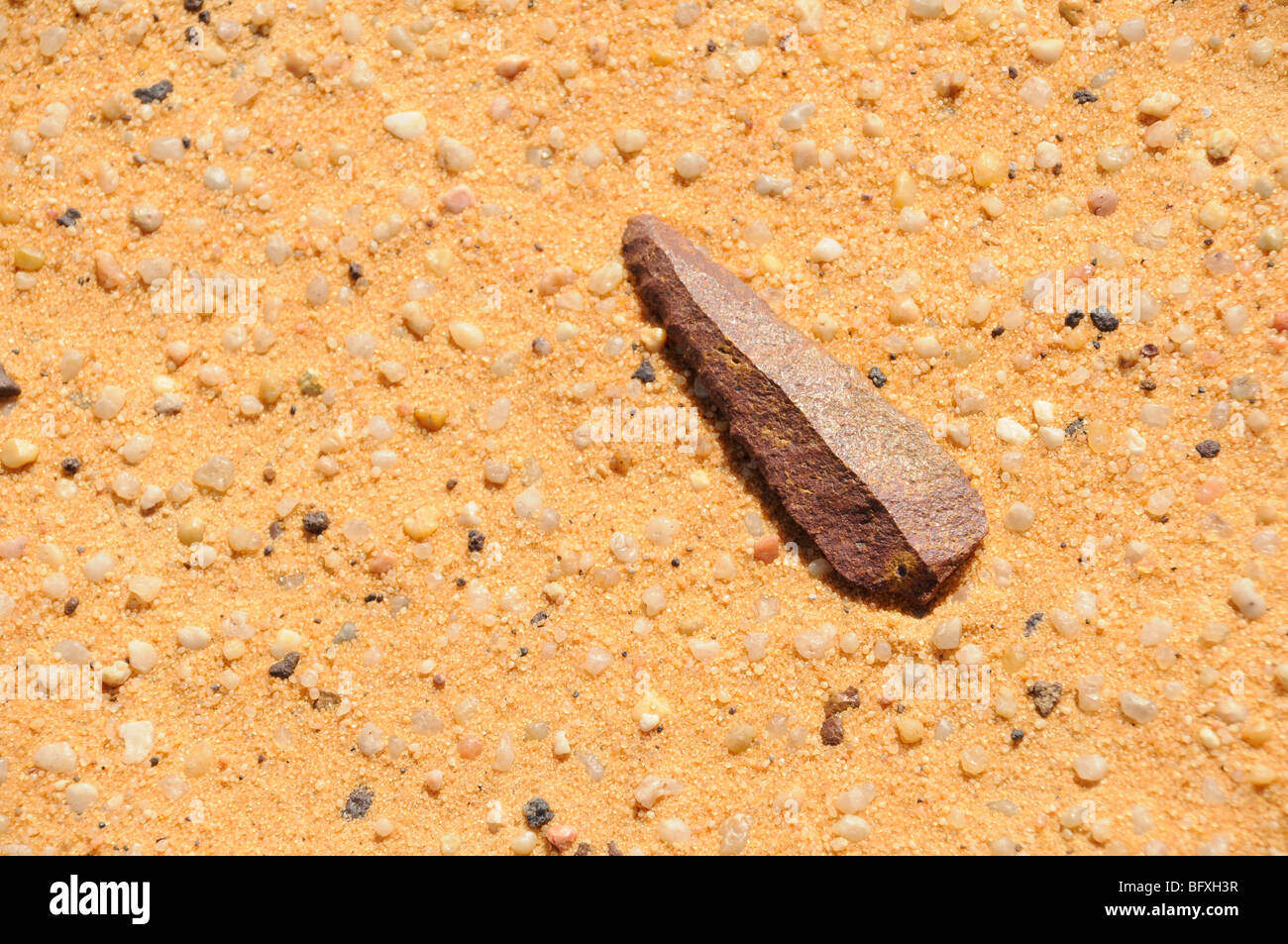 A prehistoric stone arrowhead or spearhead found in the sand of the Gilf Kebir area of the Sahara Desert, in the - Stock Image