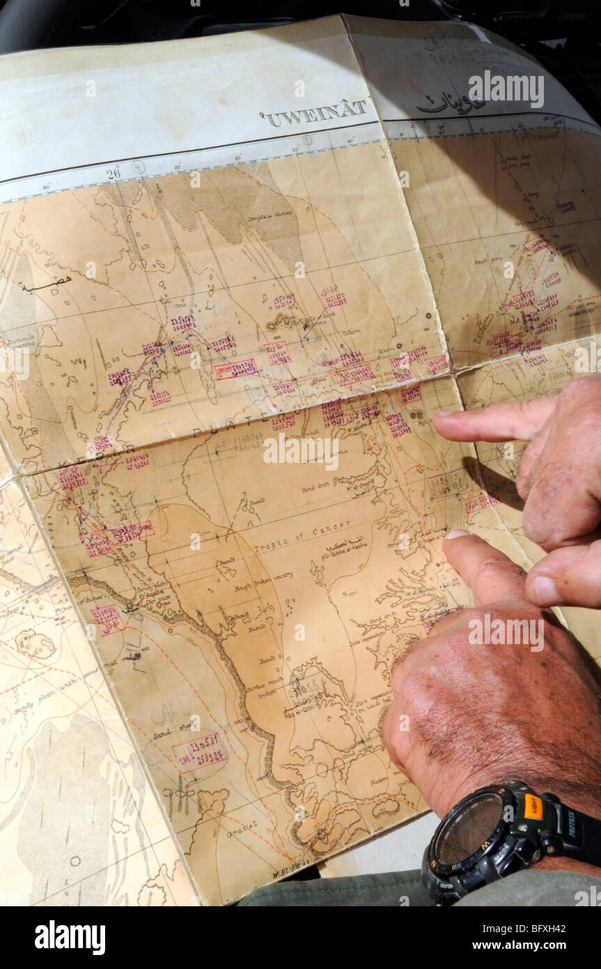 A desert safari leader plans his route on a map of the Gilf Kebir and Jebel Uweinat area of the Sahara Desert, in - Stock Image