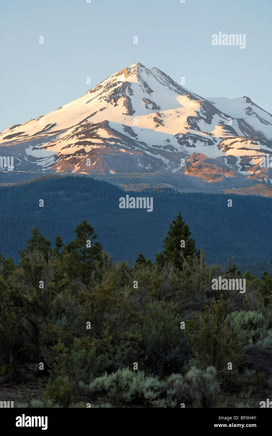 Mount Shasta being hit by the sun's morning rays. - Stock Image