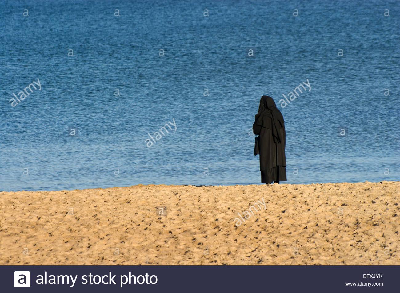 live in solitude - alone nun, sea and beach - Stock Image