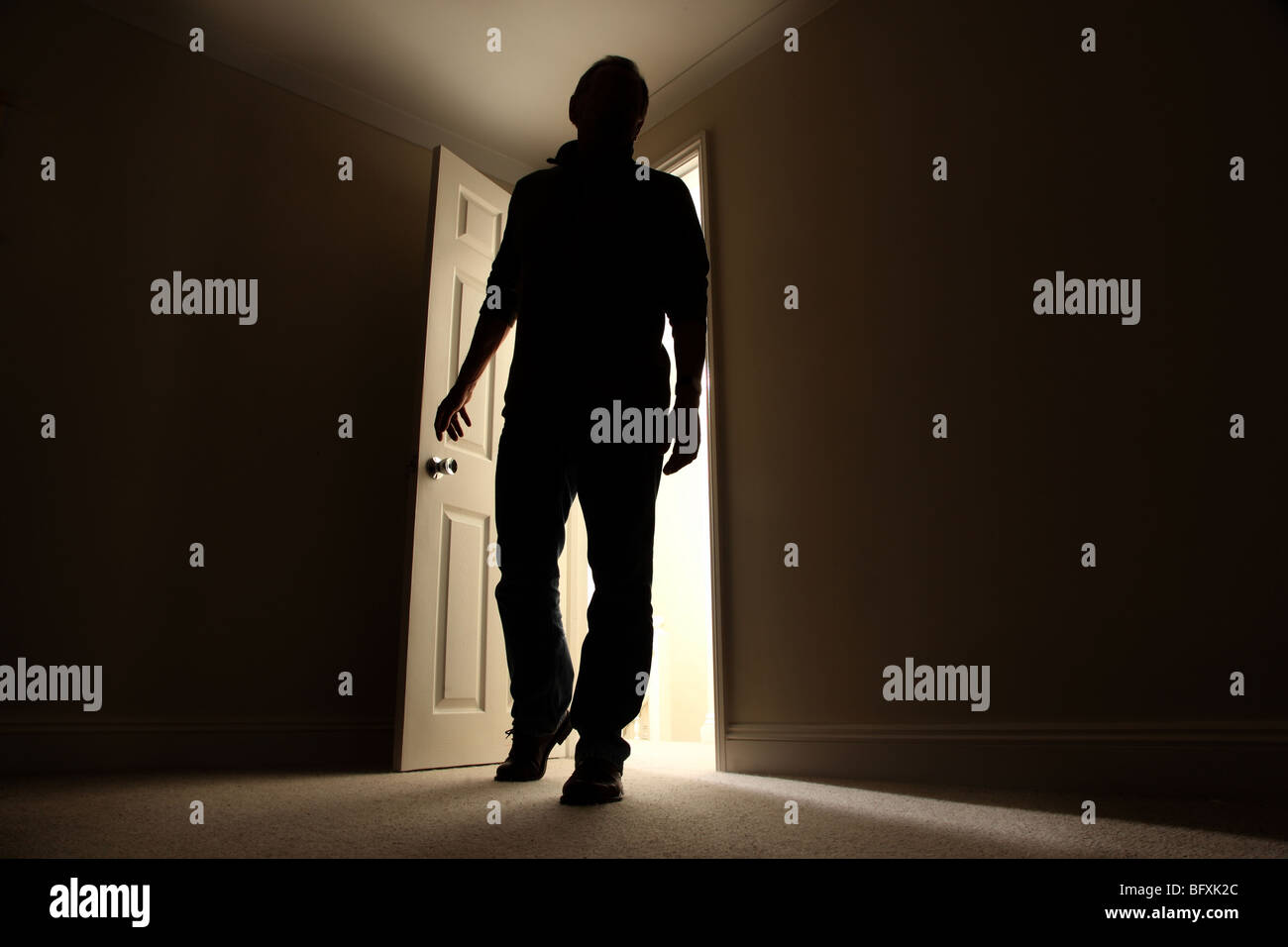 Silhouette of a male entering a dark room with a shaft of light ...