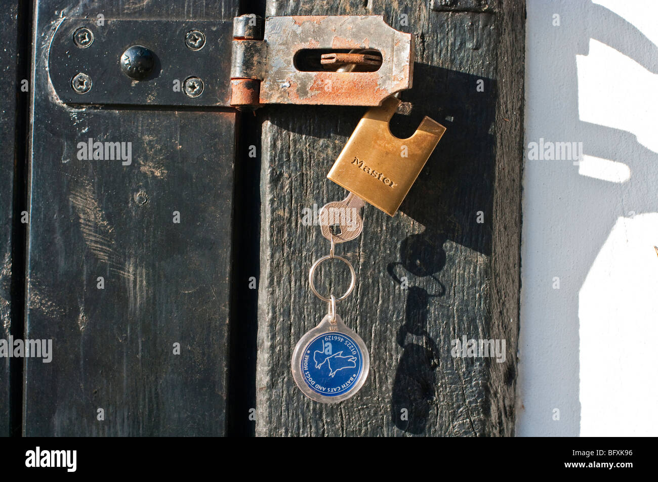 Unlocked padlock with key present inviting theft if left unattended - Stock Image