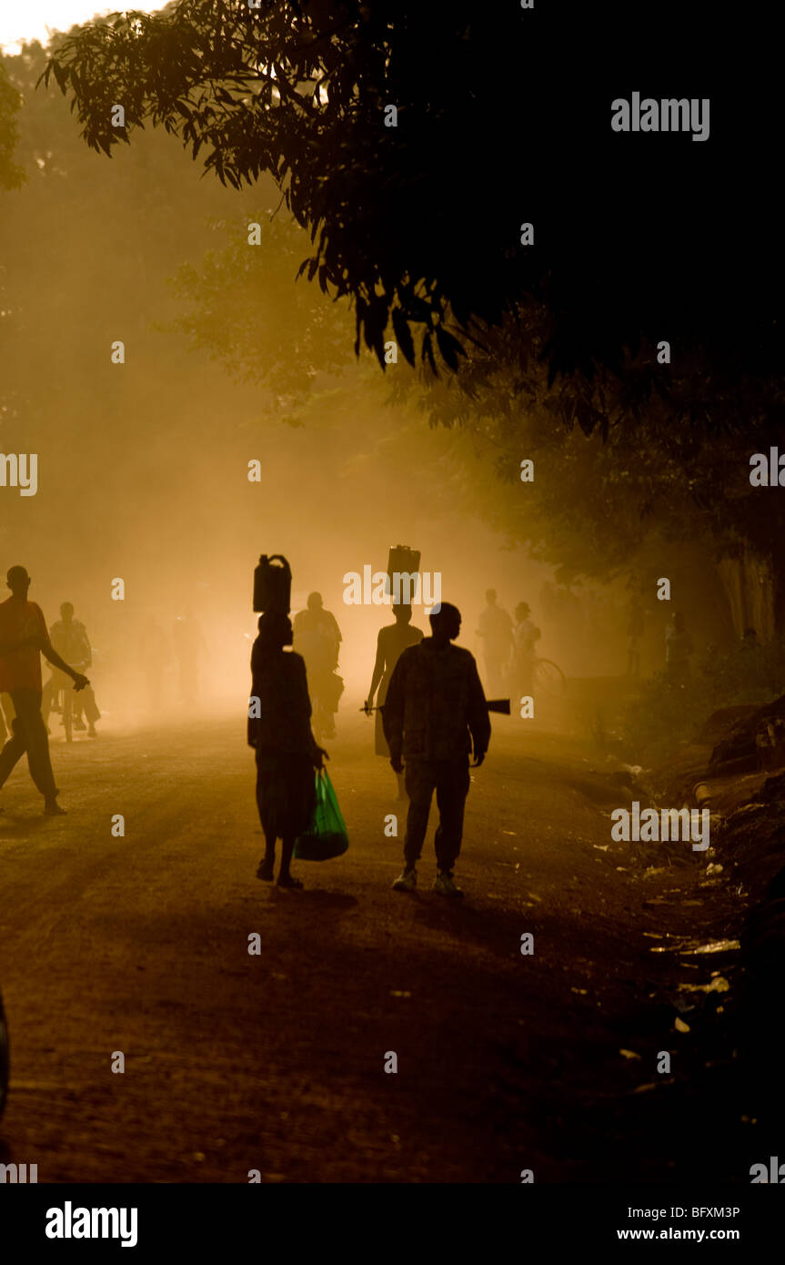 Civilian's and soldiers walk home in the sunset, Yei, South Sudan. - Stock Image