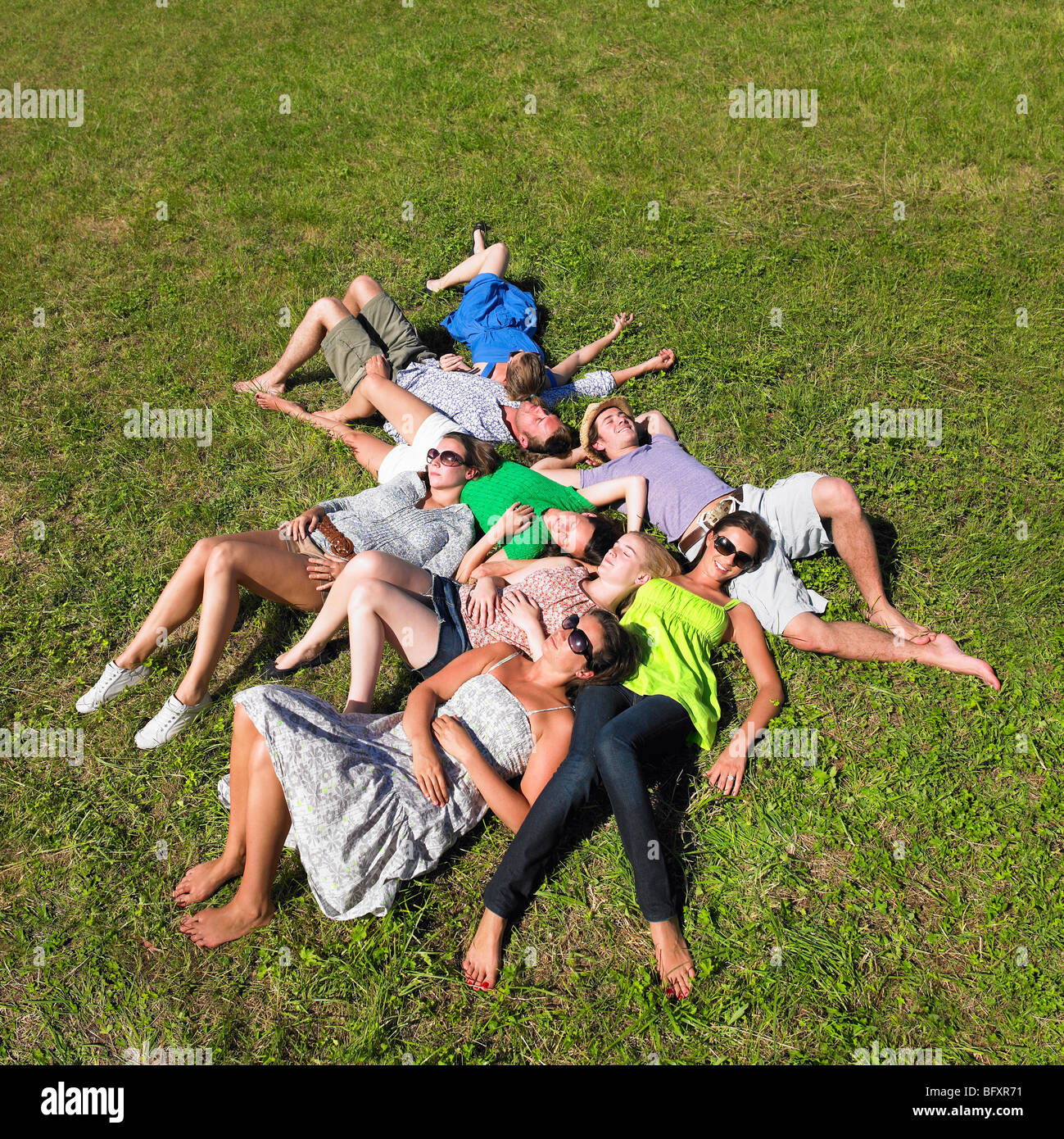 group of young people lying in field - Stock Image
