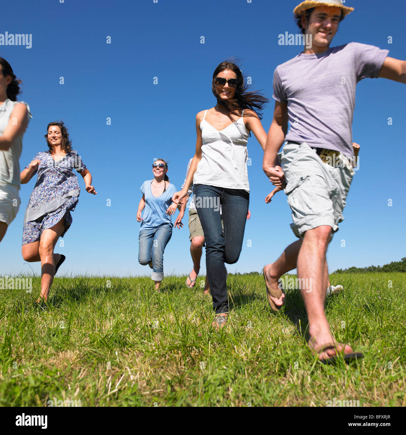 group of young people running in field - Stock Image