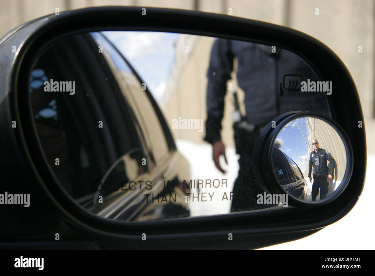 American cop reflected in car wing mirror. - Stock Image