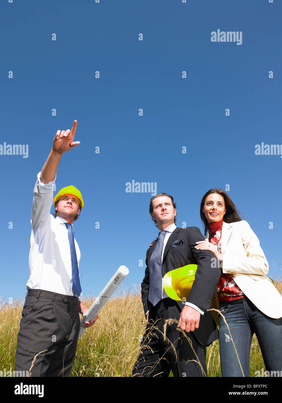 contractors with blueprints in field Stock Photo