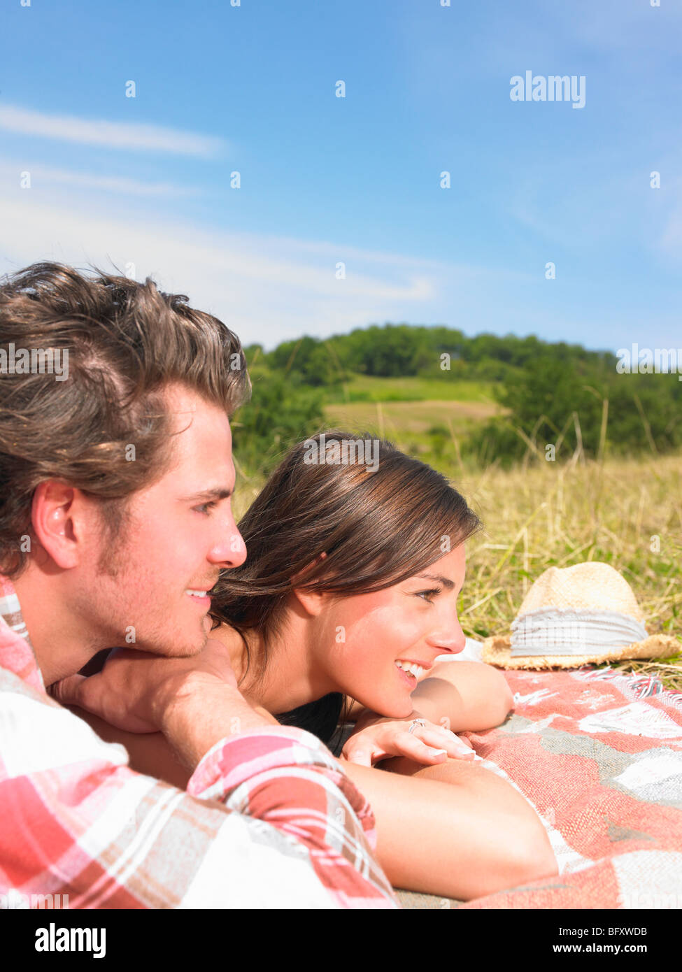 couple on blanket in field - Stock Image
