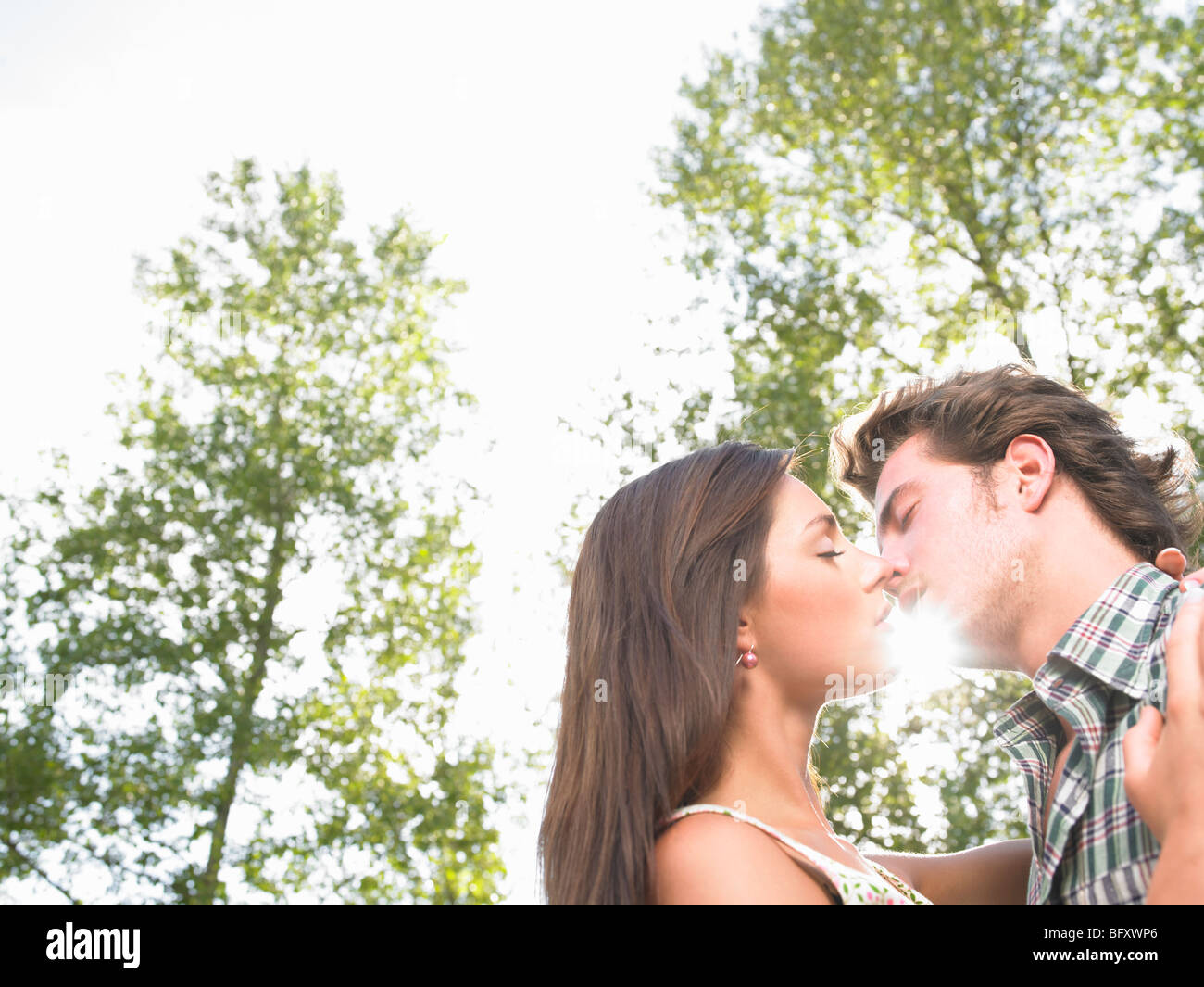 couple kissing under trees - Stock Image
