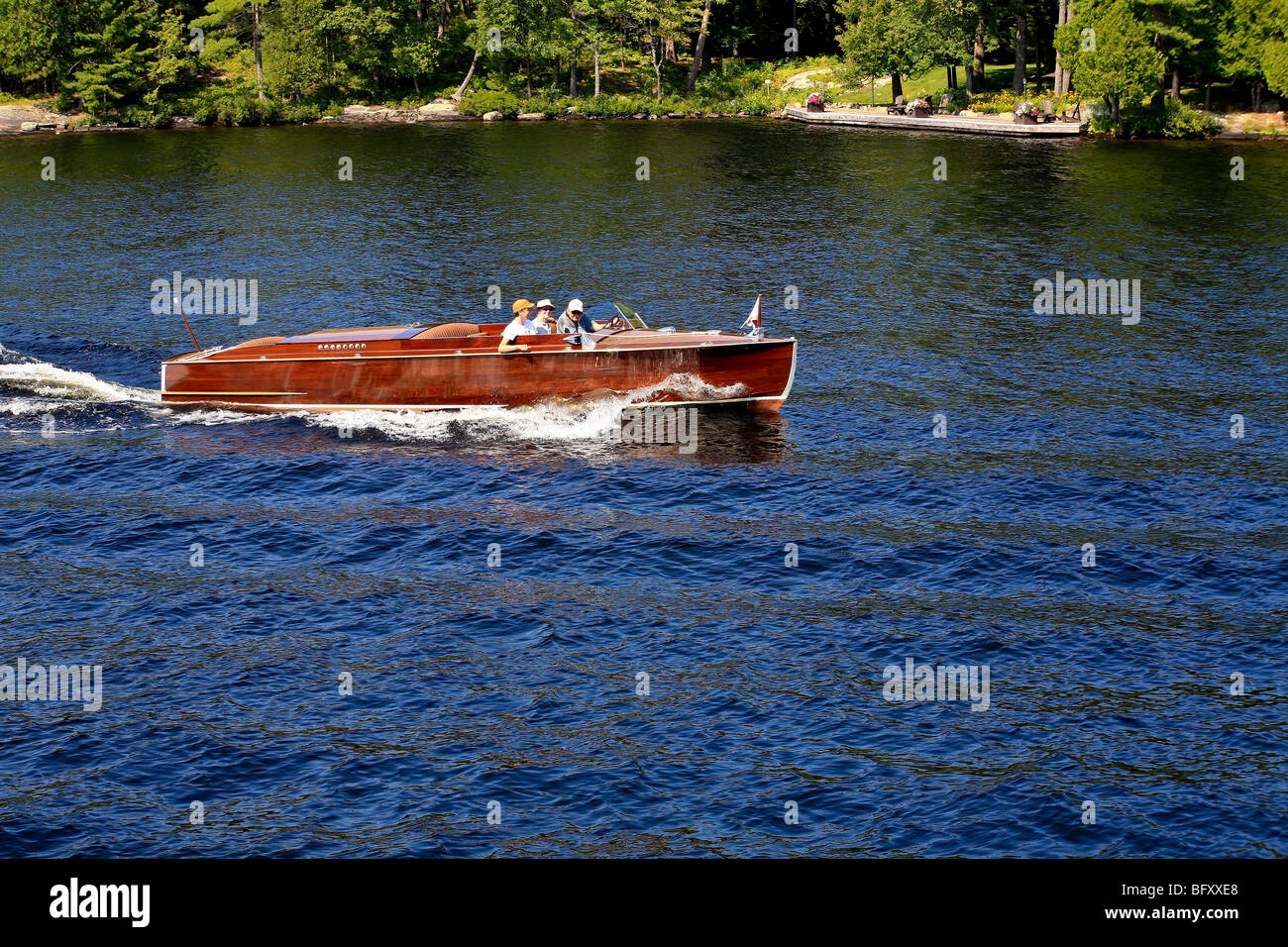 Mahoganie boat on lake in Cottage Country in the Summer on Lake Muskoka in Gravenhurst,Ontario;Canada - Stock Image