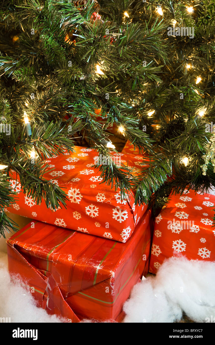 A closeup of Christmas presents under the tree, focus on the worn wrapping paper, indicating it has been re-used. - Stock Image