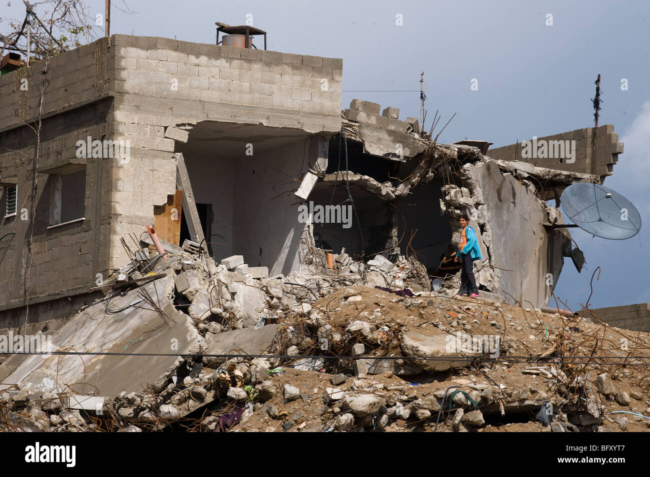 A girl stands in the ruins of her home in Jebaliya north Gaza strip after the 2009 Israel war. - Stock Image