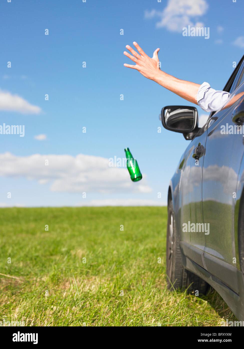 man throwing bottle away - Stock Image