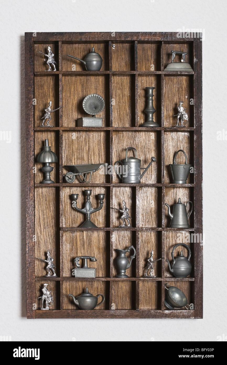 Wooden shelf with tin miniatures - Stock Image