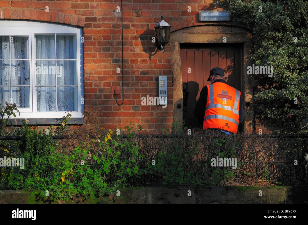 Postal Worker delivering letters - Stock Image