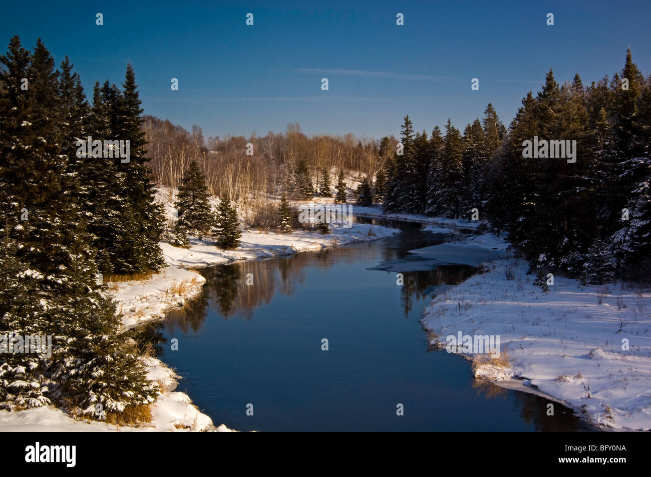 Open water of Junction Creek with snow-dusted spruces and frosted birches, Greater Sudbury, Ontario, Canada - Stock Image
