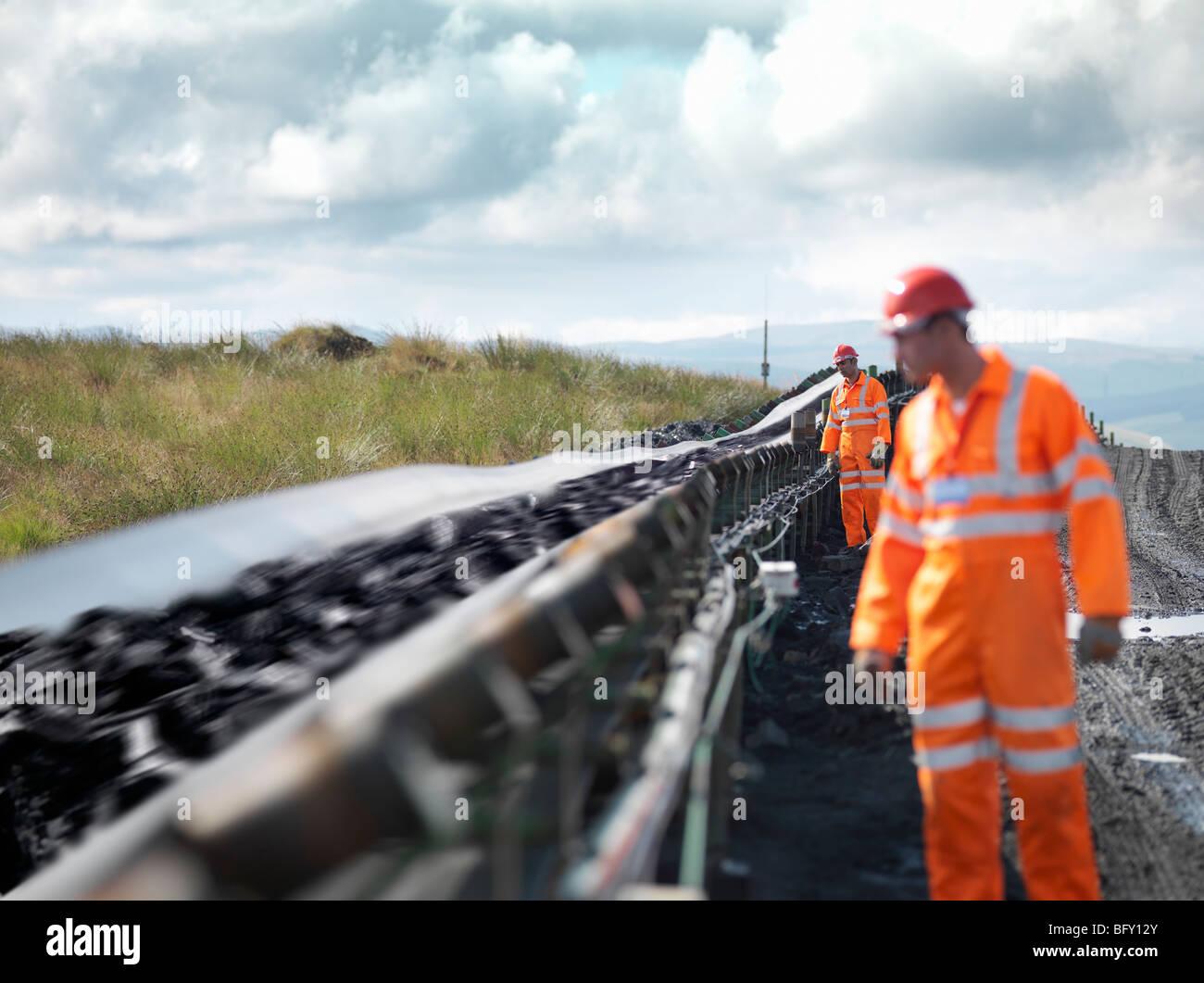 Coal Workers Inspecting Conveyor Belt - Stock Image