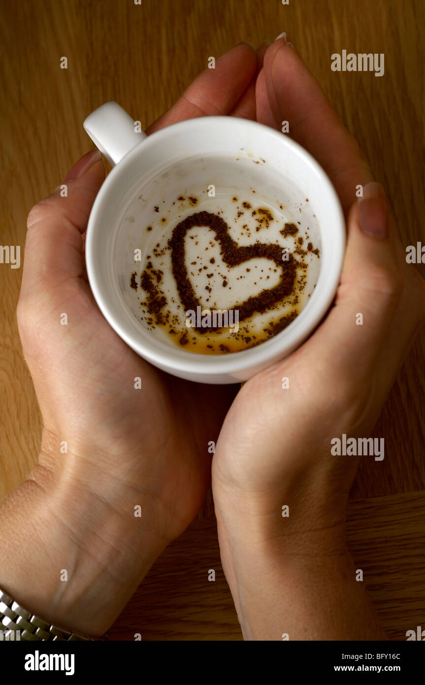 Woman looking at heart in tea leaves - Stock Image