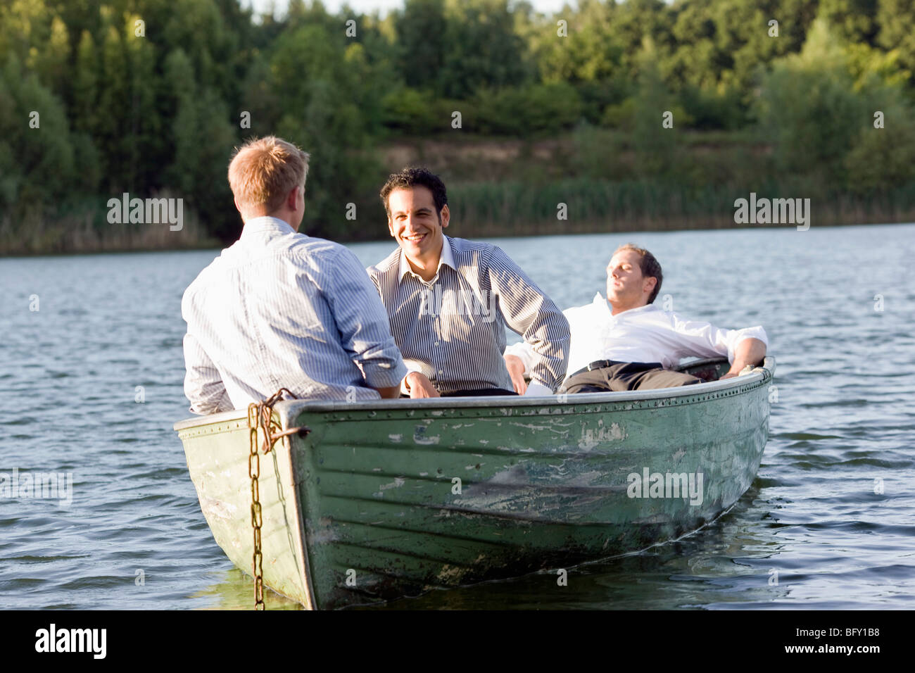 three businessmen relaxing in rowboat - Stock Image
